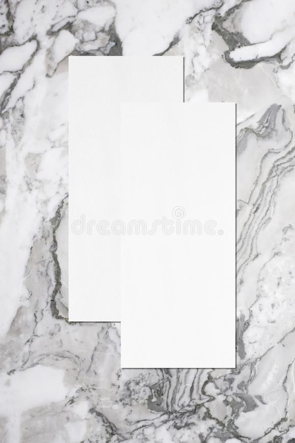 Two empty price-list or menu mockups lying on top of each other on grey marble background. Two empty price-list or menu mockups with soft shadows, lying on top royalty free stock photo