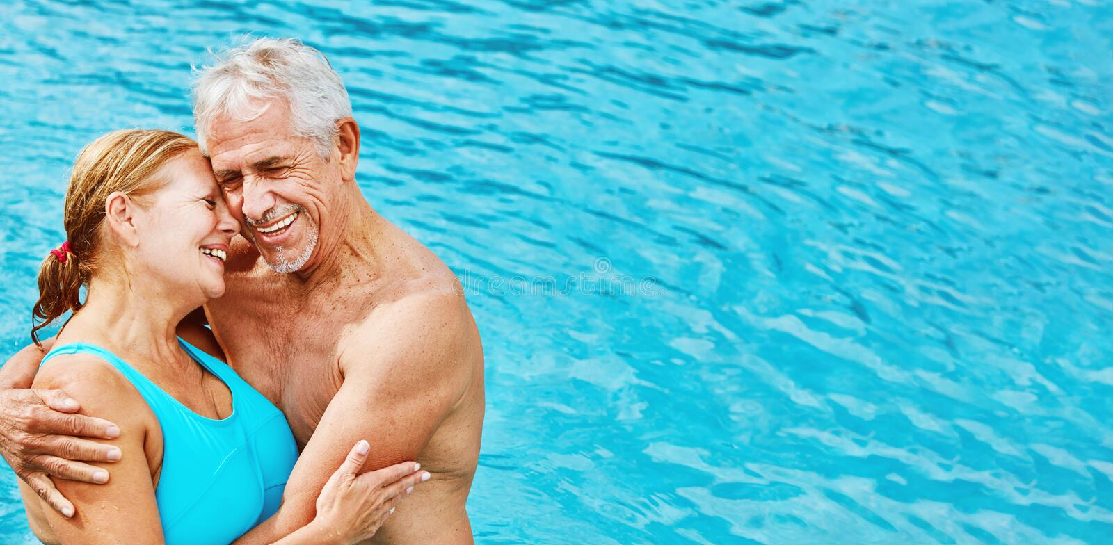 Two enamored seniors as a couple in the hotel pool royalty free stock images