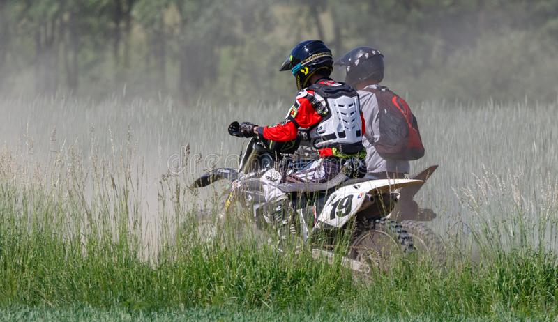 Two enduro bike riders in field stock images