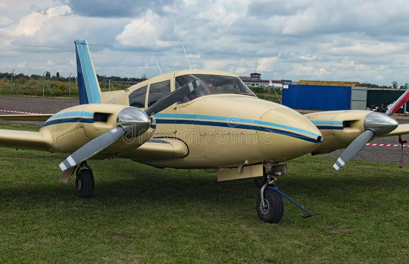The two engine plane stands on the green grass in a cloudy day. A small private airfield in Zhytomyr, Ukraine.  royalty free stock image