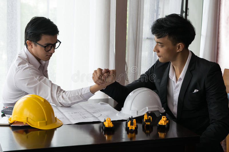 Two engineer or businessman engage in arm wrestling. Concept of battle or fighting stock photo