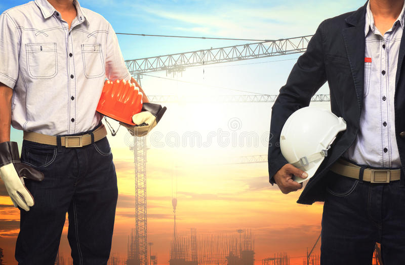 Two engineer man working with white safety helmet against crane royalty free stock photos