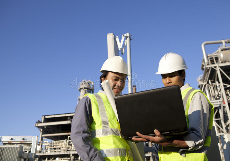 Two engineer power and energy with laptop. Two engineer power and energy discussion on location site using laptop stock photo