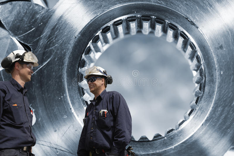 Two engineers and cogwheels axle. Two workers, engineers in front of large cogwheels axles stock photography
