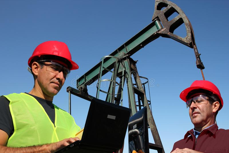 Two Engineers With Laptop Computers in the Oil Field. Engineers using laptop computers outdoors next to pump jack in the oil field royalty free stock photography