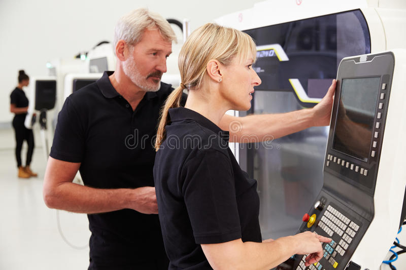 Two Engineers Operating CNC Machinery On Factory Floor royalty free stock photos