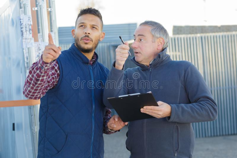 Two engineers smiling outside in shipping yard stock image