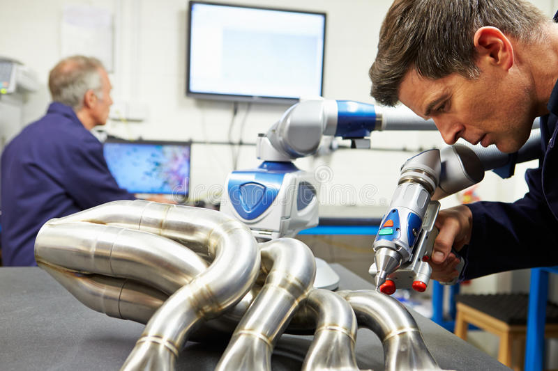Two Engineers Using Computerized CMM Arm In Factory stock photos