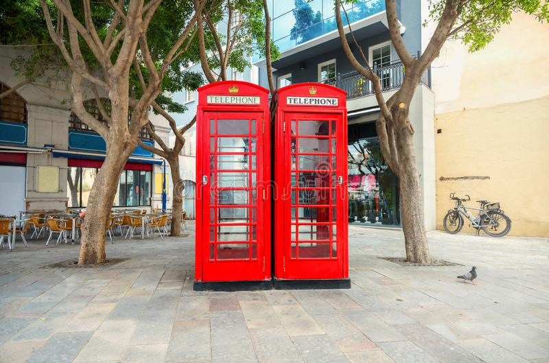 Two English red telephone boxes on street at downtown. Gibraltar. Cityscape with two English red telephone boxes on street at centre of town. Gibraltar royalty free stock image