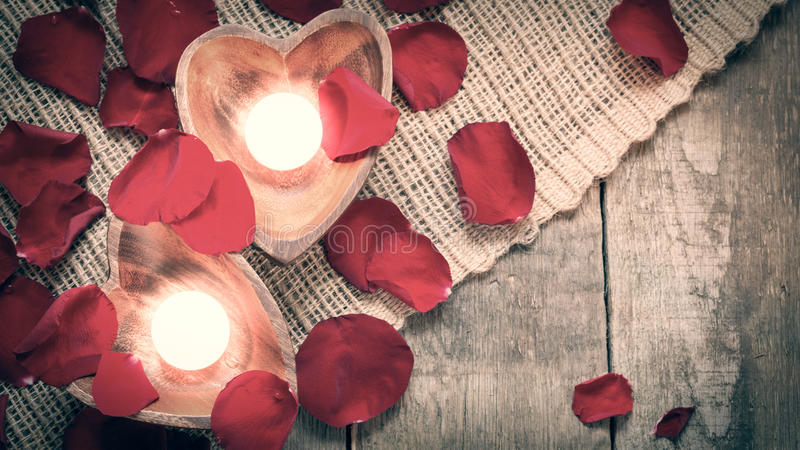 Two enlightened candles in heart-shaped candleholders with rose stock image