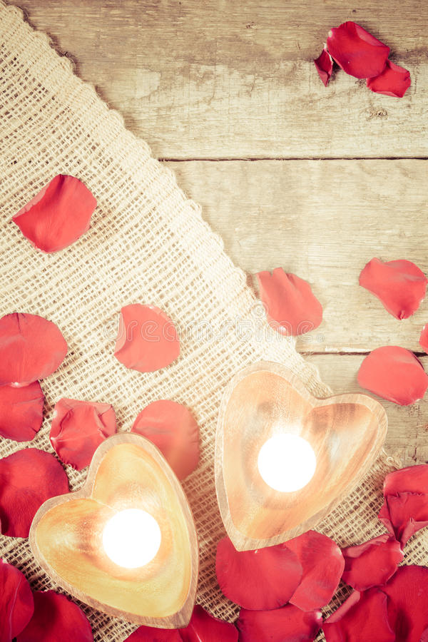 Two enlightened candles in heart-shaped candleholders with rose royalty free stock photos