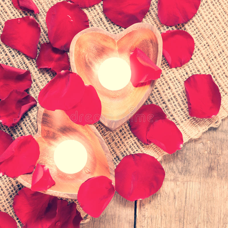 Two enlightened candles in heart-shaped candleholders with rose stock photography