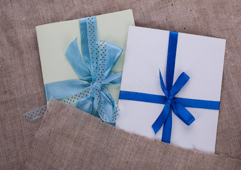 Two envelope sacking tied with ribbon