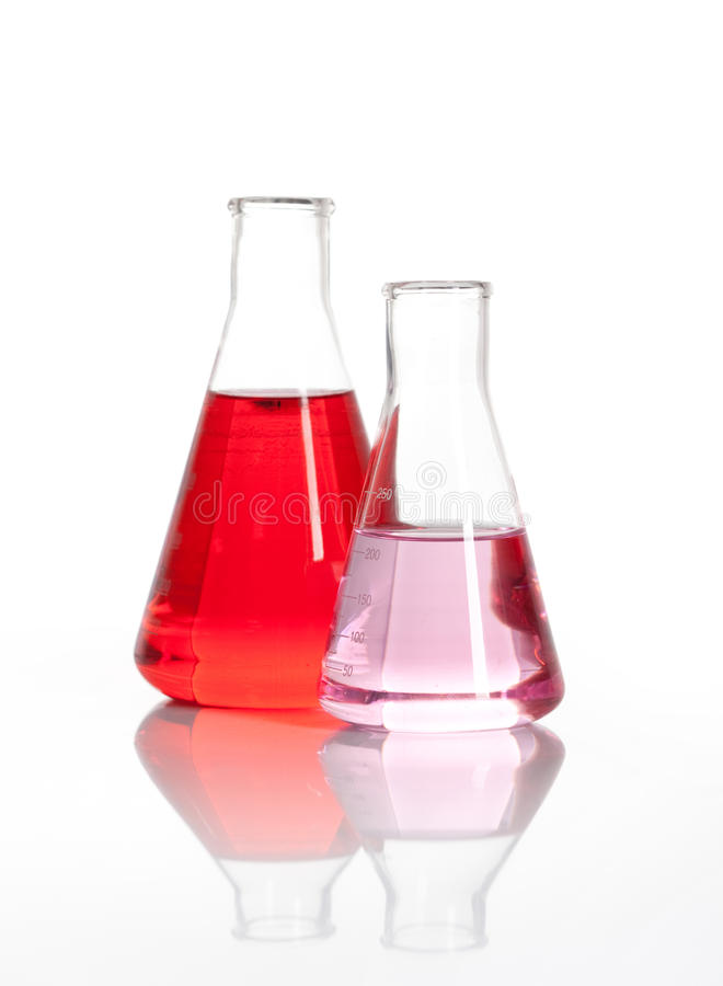 Two Erlenmeyer glass flasks with a red liquid. Two Erlenmeyer laboratory flasks with red colored chemical reagent, isolated royalty free stock images