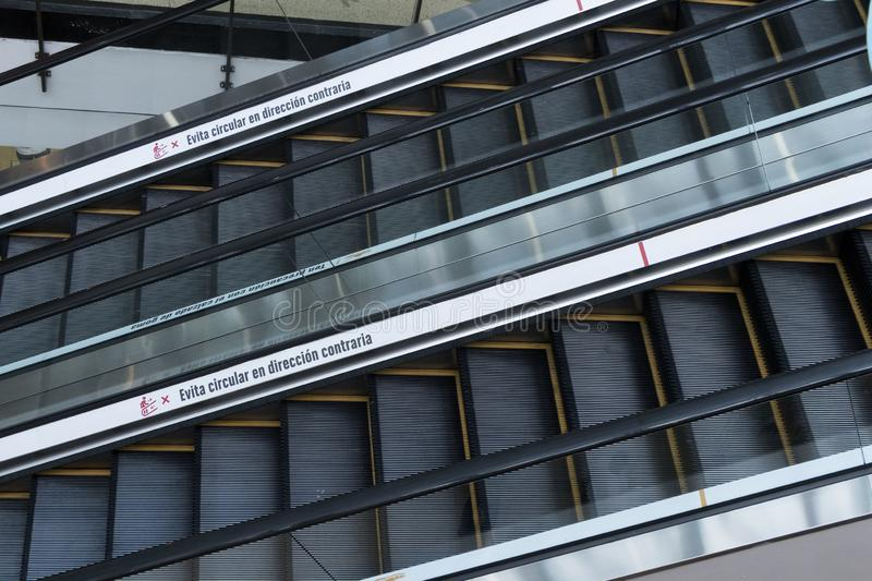 Two escalators in the foreground with a sign in Spanish that says avoid going in the opposite direction. In dark color with yellow borders stock images