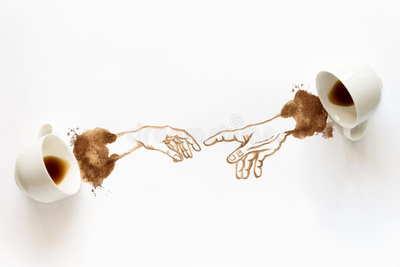 Two espresso cups with hand drawing hand to hand. Helping hands, coffee art or creative concept. Top view.  stock photo