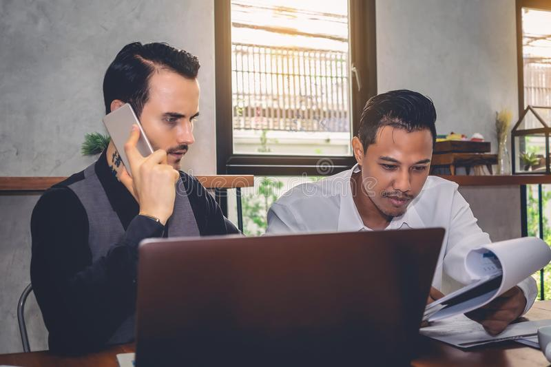 Two ethnic business people are discussing work for mutual success.Focus on Asian men stock images