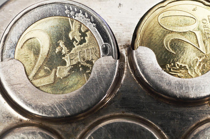 Two euro coins and twenty cents. In old coin receptacle royalty free stock photo