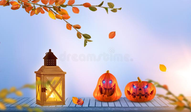 Two evilly laughing spooky scary orange pumpkins with glowing eyes on wood and lantern at evening royalty free stock photos