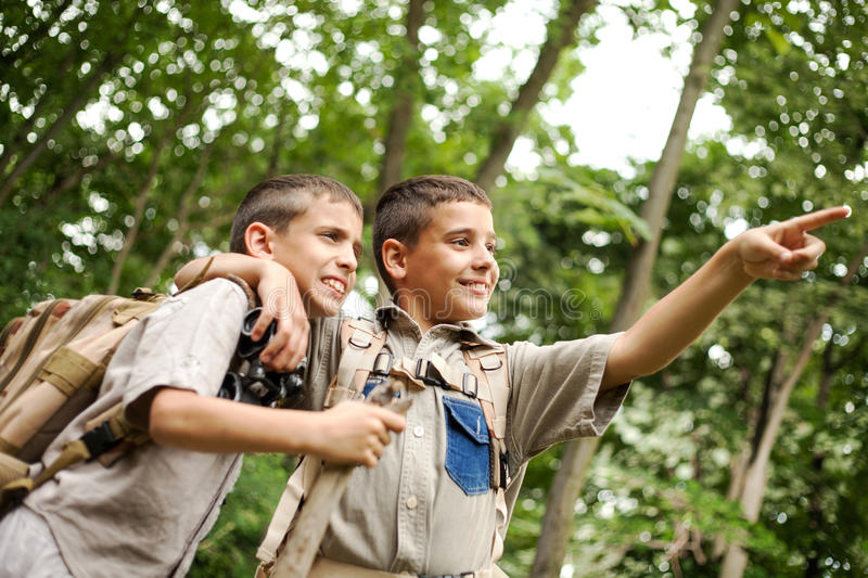 Two excited boys on a camping trip in the forest exploring. Two boys go hiking with backpacks on a forest road bright sunny day royalty free stock photo