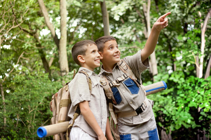 Two excited boys on a camping trip in the forest exploring. Two boys go hiking with backpacks on a forest road bright sunny day stock photography