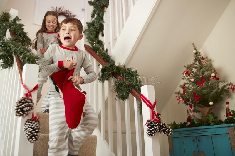 Two Excited Children Wearing Pajamas Running Down Stairs Holding Stockings On Christmas Morning stock photo
