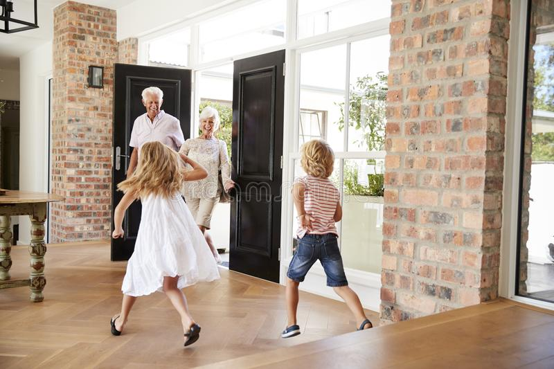 Two excited kids rush to meet their visiting grandparents royalty free stock image