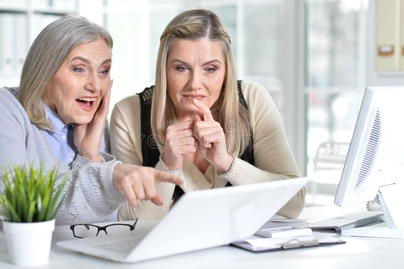 Two excited mature women working in office. With modern devices stock photography