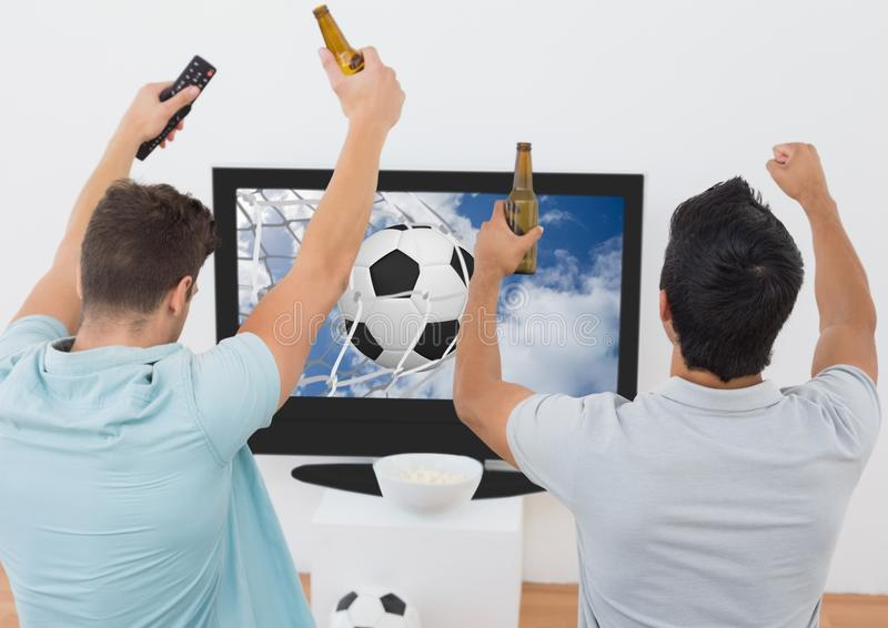 Two excited men cheering with beer bottle while watching sport match on tv. At home royalty free stock image