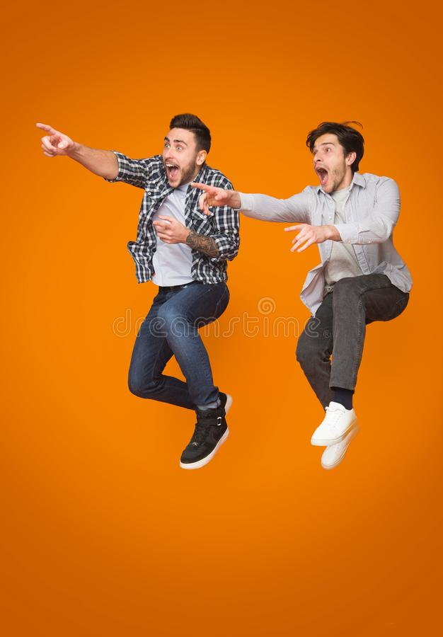Two excited men pointing fingers away, jumping over background. Two excited men pointing fingers away, jumping over orange background royalty free stock photography