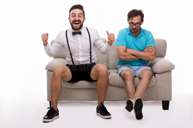 Two excited men sitting on couch. Picture of two excited men sitting on couch or sofa and looking at camera isolated on white background. Man in glasses looking royalty free stock photos