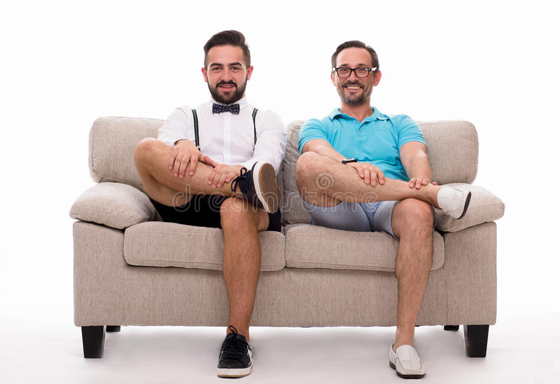 Two excited men sitting on couch. Or sofa and looking at camera isolated on white background. Happy men smiling and watching TV. Epressing emotions concept stock photos