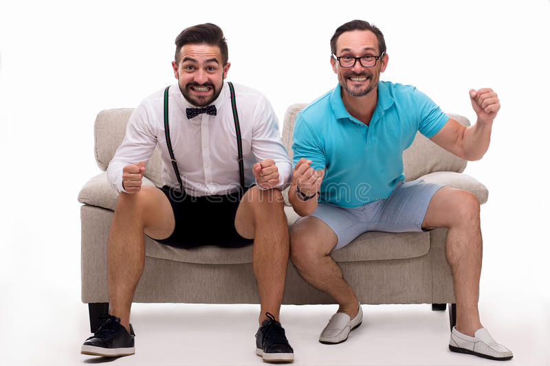 Two excited men sitting on couch. And watching favorite team soccer with goal. Happy men expressing positive emotions in studio royalty free stock images
