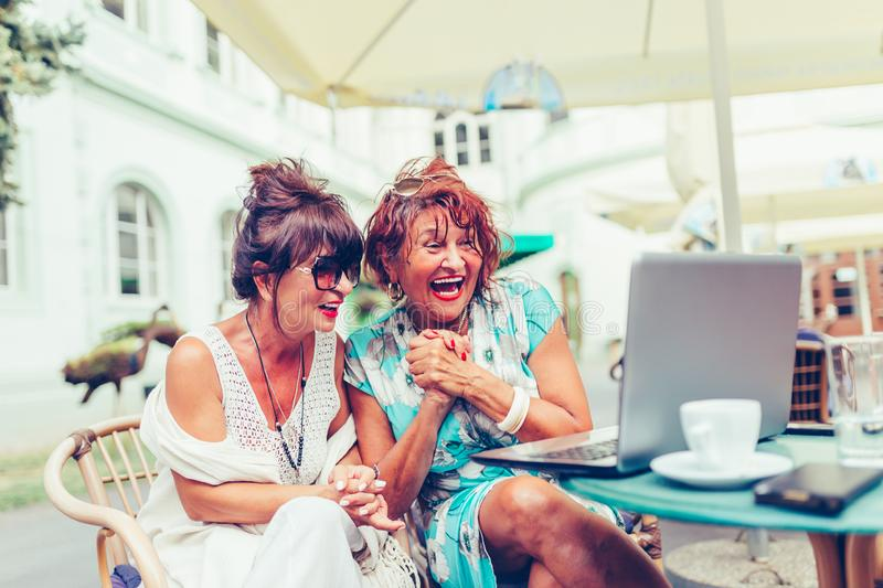 Two excited senior women reading good news on line with a laptop  in cafe stock image