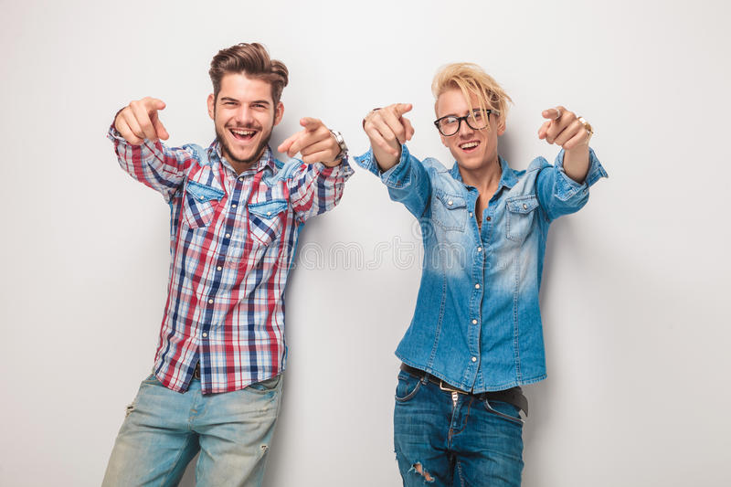 Two excited young casual men pointing fingers. To the camera in studio royalty free stock photography