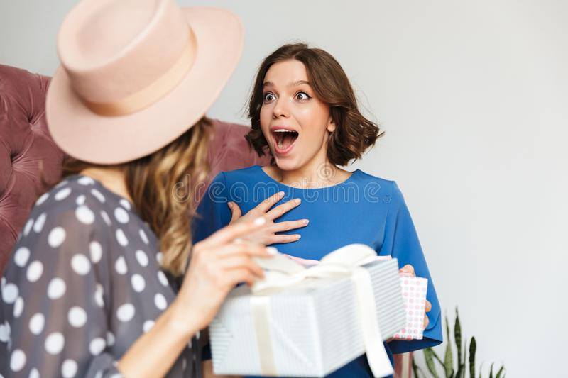 Two excited young women shopaholics holding surprise present boxes. stock images