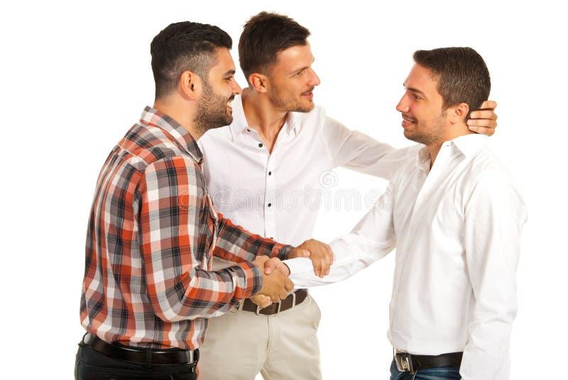 Two executives congratulate their colleague stock images