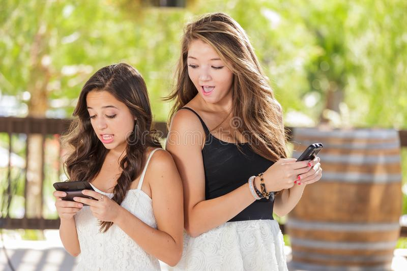 Two Expressive Mixed Race Girlfriends Texting on Their Smartphones. Two Expressive Mixed Race Girlfriends Using Their Smart Cell Phones Outdoors stock photos