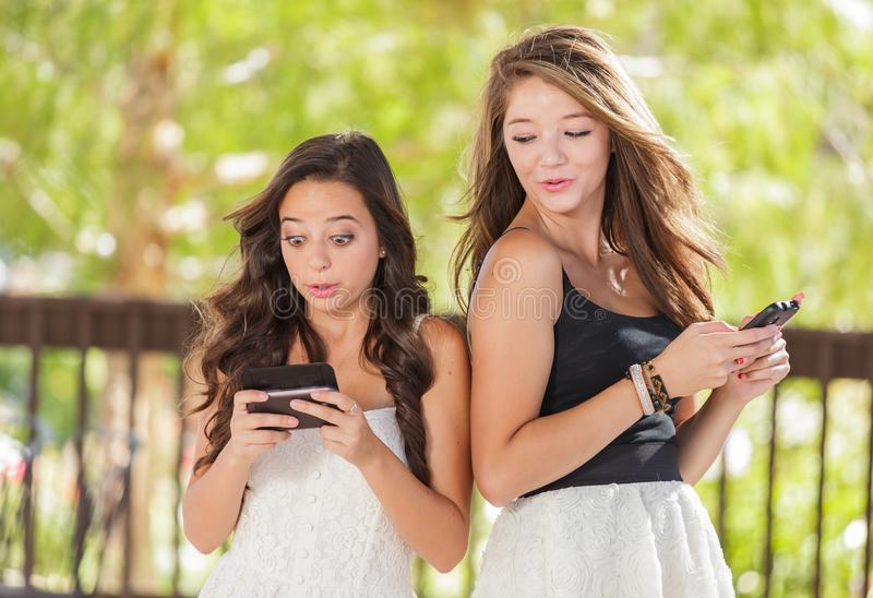Two Expressive Mixed Race Girlfriends Texting on Their Smartphones. Two Expressive Mixed Race Girlfriends Using Their Smart Cell Phones Outdoors stock photography