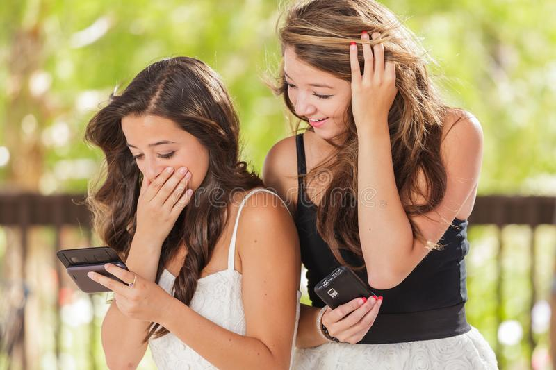Two Expressive Mixed Race Girlfriends Using Their Smart Cell Phones Outdoors stock photography