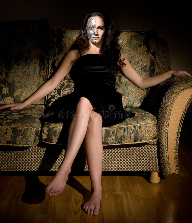 Two-faced Woman Sitting On The Sofa Royalty Free Stock Images