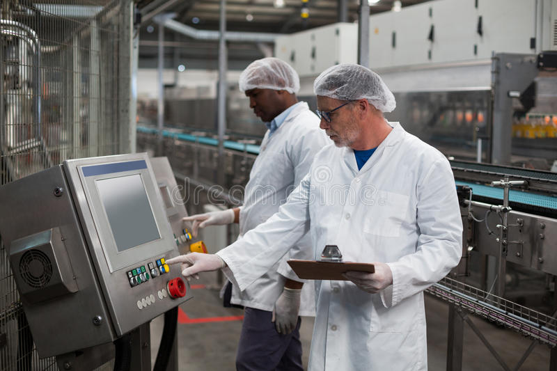 Two factory engineers operating machine in factory. Two factory engineer operating machine in drinks production plant royalty free stock image