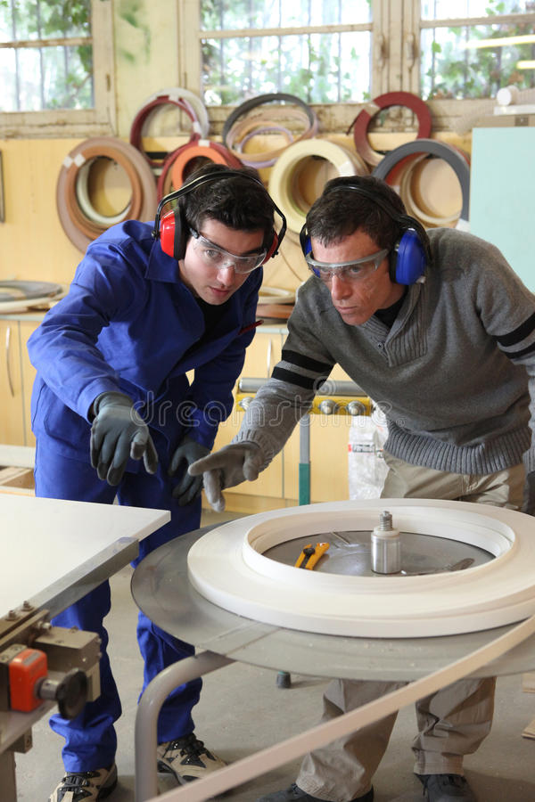 Two factory workers. Looking voer plans stock photos
