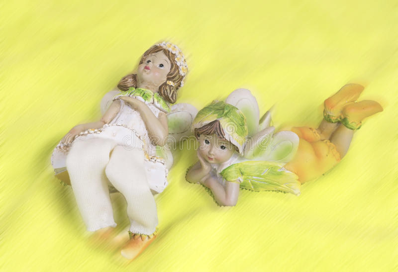 Two fairies lying and dreaming. Two fairies statues - girls with wings royalty free stock image