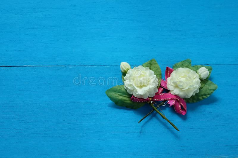Two fake jasmine flowers d on wooden blue background. Two fake jasmine flowers made from fabrics placed on wooden blue background stock image