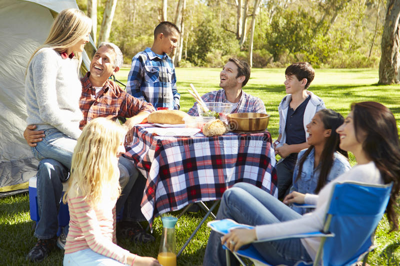 Two Families Enjoying Camping Holiday In Countryside. Two Happy Families Enjoying Camping Holiday In Countryside Smiling At Each Other royalty free stock photography