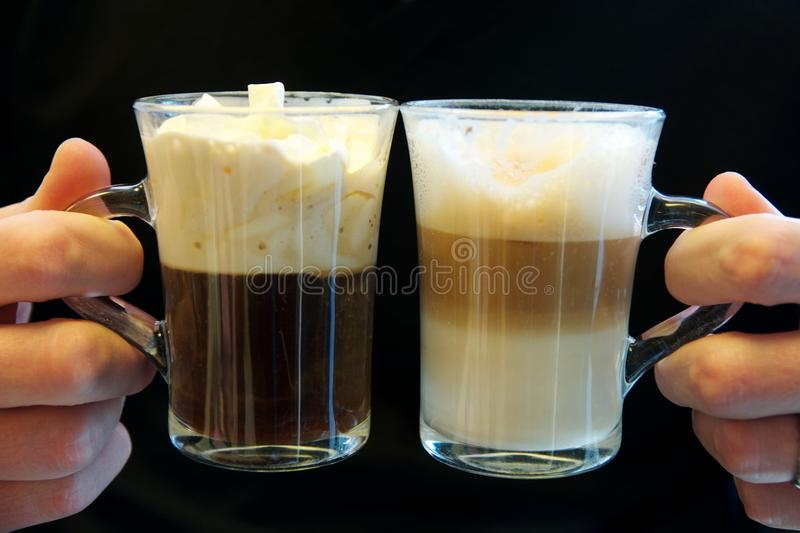 Two fancy coffees in glass cups, held by two hands. Two different handheld fancy coffees from a Viennese konditorei meet against a black background stock images