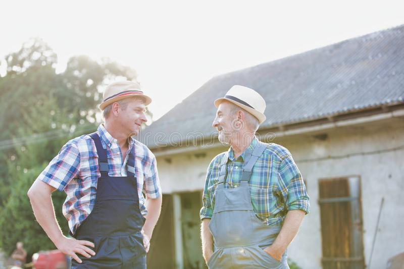 Two farmers talking against barn. Photo of Two farmers talking against barn stock images