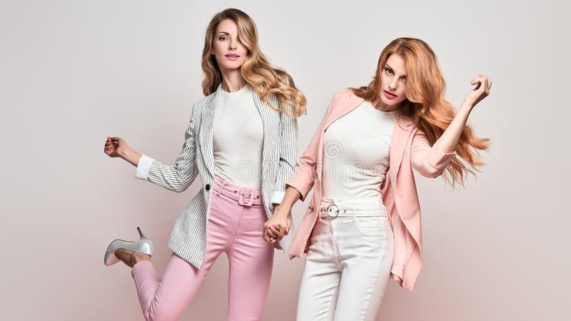 Two Fashion autumn having fun, Trendy fall outfit. Fashionable autumn women dance having fun with stylish hairstyle, fall makeup. Two Excited funny Girl, Trendy royalty free stock image