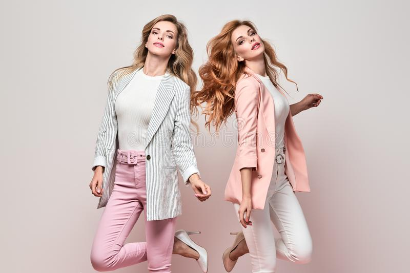 Two Fashion autumn having fun, Trendy fall outfit. Fashionable autumn women dance having fun with stylish hairstyle, fall makeup. Two Excited funny Girl, Trendy stock images